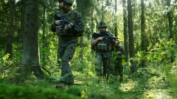 Squad of Five Fully Equipped Soldiers on a Reconnaissance Military Mission. Theyre Moving in Formation Through Dense Forest. Long Shot Footage.
