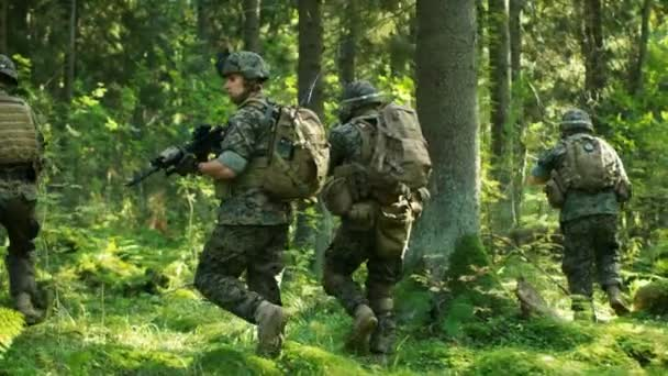 Squad of Five Fully Equipped Soldiers in Camouflage on a Reconnaissance Military Mission, Rifles in Firing Position. Theyre Moving in Formation Through Dense Forest. Following Back View Shot Slow Motion.