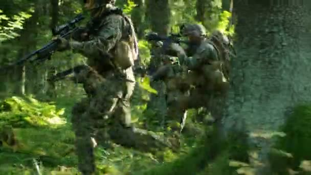 Military Operation in Action, Squad of Five Fully Equipped Soldiers Wearing Camouflage Uniform Attacking Enemy, Rifles in Firing Position. Theyre Running in Formation Through Dense Forest. Side View Long Shot.