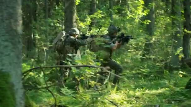 Squad of Five Fully Equipped Soldiers in Camouflage on a Reconnaissance Military Mission, Rifles in Firing Position. Theyre Running in Formation Through Dense Forest. Side View Long Shot.