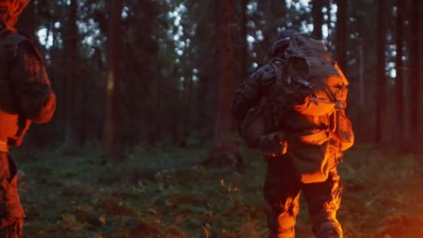 Squad of Five Fully Equipped Soldiers in Camouflage on a Reconnaissance Military Night Mission. Theyre Lit by Red Flare and Move Through Dense Forest.