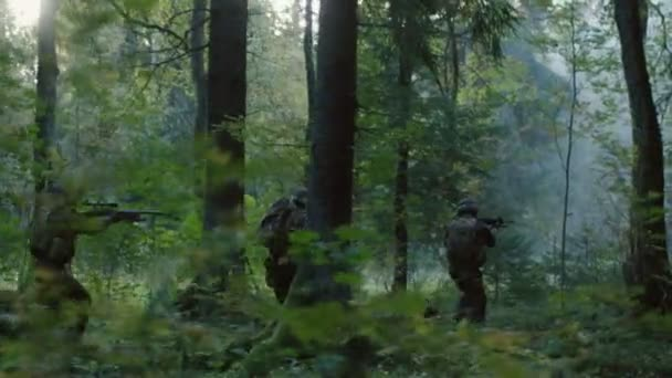 Fully Equipped Soldiers Wearing Camouflage Uniform Attacking Enemy, Rifles in Firing Position. Military Operation in Action, Squad Running in Formation Through Dense Forest. Side View Long Shot.