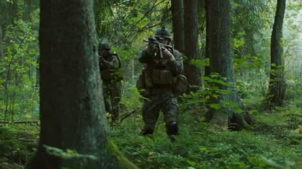Fully Equipped Soldiers Wearing Camouflage Uniform Attacking Enemy, Rifles in Firing Position. Military Operation in Action, Squad Running in Formation Through Dense Forest.