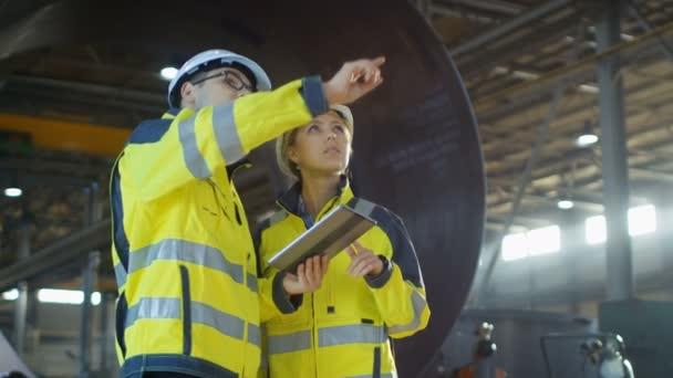 Mužské a ženské průmyslové inženýry v tvrdé klobouky diskutovat o novém projektu při použití tabletového počítače. Pracují v těžkém průmyslu výrobního závodu