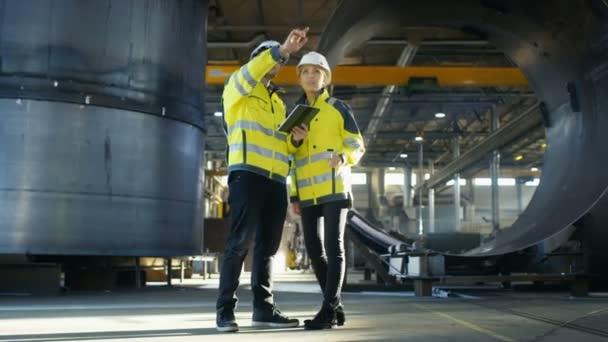 Mužské a ženské průmyslové inženýry v tvrdé klobouky diskutovat o novém projektu při použití tabletového počítače. Dělají, ukazující Gestures.They práce v těžkém průmyslu výrobní továrny. Podnik s nejistým výsledkem