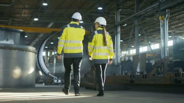 Pohled zezadu záběr mužských a ženských s diskuse při chůzi přes těžký průmysl továrny vyrábějící průmyslové inženýry. Velké zámečnické konstrukce, potrubí prvky ležící kolem