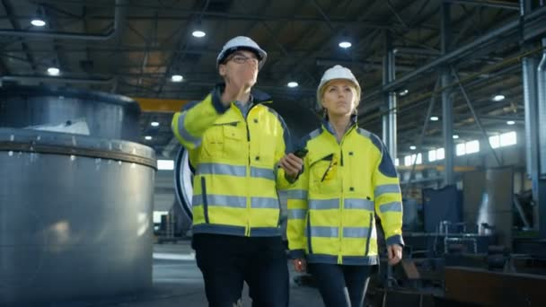 männlicher Projektmanager mit Handy und weibliche Wirtschaftsingenieurin diskutieren, während sie durch die Produktionsfabrik der Schwerindustrie gehen. große Metallkonstruktionen, herumliegende Rohrleitungselemente.