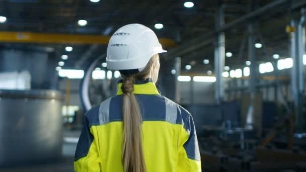 Po výstřelu průmyslové zaměstnankyně v přilbu procházky po těžkém průmyslu továrny vyrábějící. V pozadí projektu různé zámečnické díly ležící