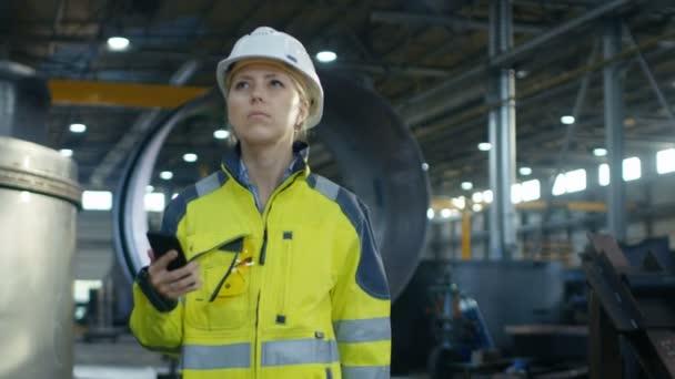 Weibliche Industriearbeiter in den Schutzhelm nutzt Handy bei einem Spaziergang durch Schwerindustrie Manufacturing Factory. Im Hintergrund verschiedene Metallarbeiten Projekt Teile liegen