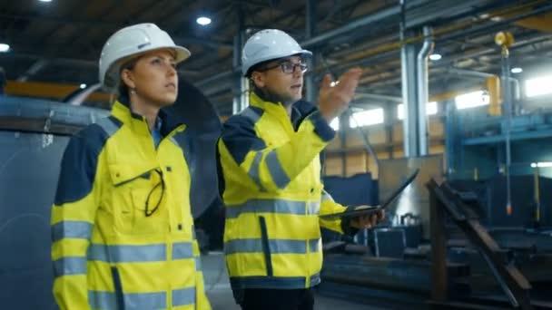 Mužské a ženské průmyslové inženýry v Belfastu a bezpečnostní vesty diskutovat o nový projekt při používání notebooku. Projít na těžký průmysl, výrobní továrna s kovových komponent povalovat
