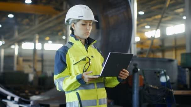 Weibliche Wirtschaftsingenieur in der Schutzhelm und Sicherheit Jacke verwendet Laptop-Computer in der Schwerindustrie Herstellung Fabrik stehen. Im Hintergrund verschiedene Metallarbeiten Projekt Teile liegen