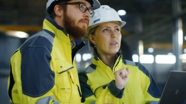Portrét muže a ženy průmyslové inženýry v tvrdé klobouky diskutovat o novém projektu při používání notebooku. Nosí bezpečnostní Jackets.They práce na těžký průmysl, výrobní továrny. Podnik s nejistým výsledkem
