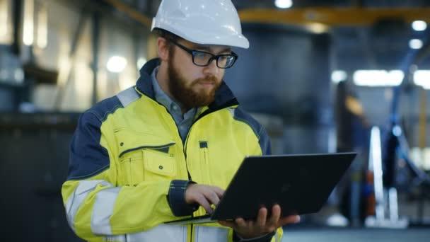 Industrieingenieur in Hard Hat tragen Sicherheitsjacke verwendet Laptop. Er arbeitet in der Schwerindustrie-Fertigungsfabrik mit verschiedenen Metallbearbeitungsprozessen sind im Gange.