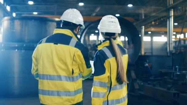 Samec a samice Šingó používání notebooku a mají diskuse při chůzi přes těžkého průmyslu výrobní továrna. Nosí tvrdě, klobouky a bezpečnostní vesty. Na pozadí velké zámečnické konstrukce, komponenty příležitostí