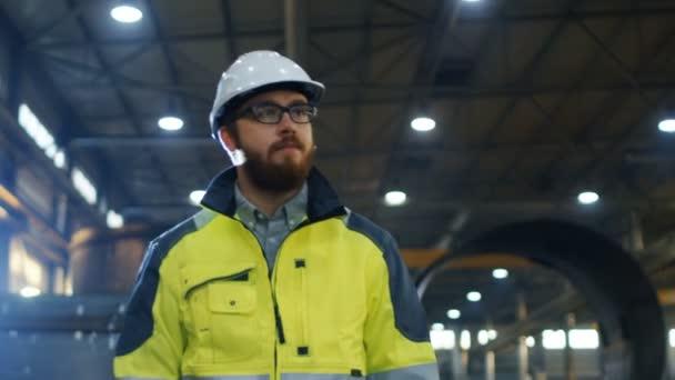 Průmyslový inženýr v přilbu nosit bezpečnostní bunda vlny ruku na pozdrav a procházky po těžkém průmyslu výrobního závodu s různými objemového tváření