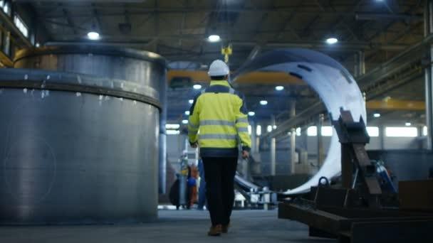 Zadní pohled na průmyslový inženýr v přilbu nosit bezpečnostní bunda procházky po těžkém průmyslu výrobního závodu s různými objemového tváření