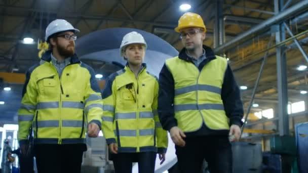 Folgenden Schuss von drei Ingenieuren zu Fuß durch Schwerindustrie Manufacturing Factory. Im Hintergrund Work In Progress, verschiedene Metallarbeiten, Pipeline Schweißen / Fass Komponenten. Slow-Motion.