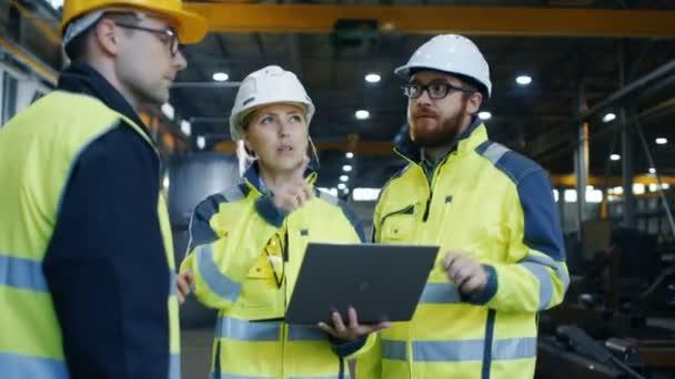 Wirtschaftsingenieurinnen und Wirtschaftsingenieure unterhalten sich mit Fabrikarbeitern, während sie Laptops benutzen. Sie arbeiten in der Schwerindustrie.