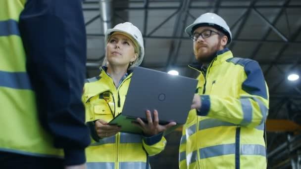 Mužské a ženské průmyslové inženýry, promluvit si s tovární dělník při používání notebooku. Pracují na těžký průmysl, výrobní zařízení. Nízký úhel záběru