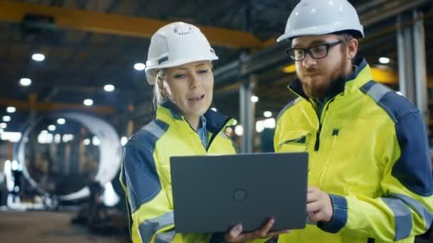In der schweren Industriefabrik hält eine Wirtschaftsingenieurin einen Laptop in der Hand und diskutiert mit dem Projektleiter. Sie tragen harte Hüte und Sicherheitsjacken. im Hintergrund Schweißen / Metallbau im Gange.
