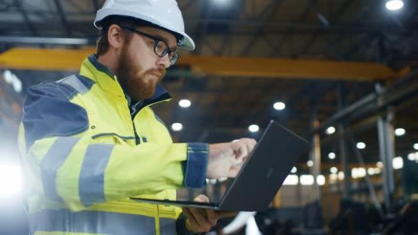 Industrial Engineer v přilbu nosit bezpečnostní vestu používá Touchscreen laptopu. Pracuje na těžký průmysl, výrobní továrny. V pozadí svařování / obráběcí procesy jsou v průběhu