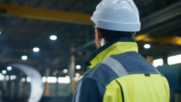 Inženýr v přilbu a bezpečnostní vestu vypadá velké těžkého průmyslu výrobní továrny. ARC View záběry