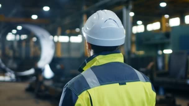 Inženýr v přilbu a bezpečnostní vestu vypadá velké těžkého průmyslu výrobní továrny. ARC View záběry.