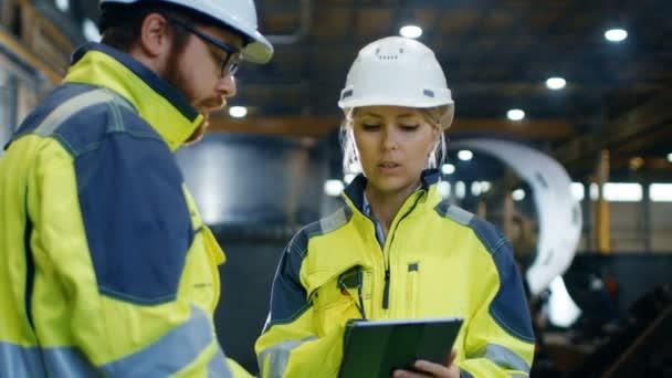 Mužské a ženské průmyslové inženýry v Belfastu a bezpečnostní vesty diskutovat o nový projekt při použití tabletového počítače. Pracují na těžký průmysl, výroba Factory