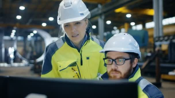 Der männliche Wirtschaftsingenieur arbeitet am Personal Computer, während die weibliche Führungskraft über Projektdetails spricht. Sie arbeiten in einer Fabrik für Schwerindustrie.