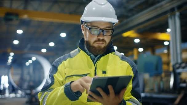 Wirtschaftsingenieur mit Schutzweste bedient sich eines Touchscreen-Tablet-Computers. er arbeitet in der Fabrik für Schwerindustrie.