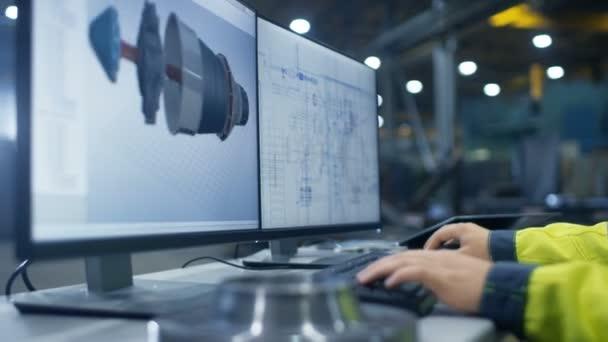Uvnitř těžkého průmyslu Factory Close-up záběry rukou průmyslový inženýr pracující na osobní počítač se dvěma monitory, navrhování turbína / motoru v 3d, pomocí programu Cad
