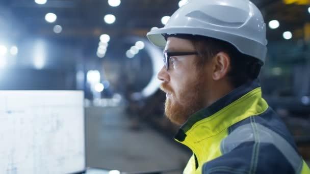 Der Wirtschaftsingenieur mit Hut, Sicherheitsjacke und Brille lächelt in die Kamera. Er arbeitet in einer großen Schwerindustrie-Fabrik.