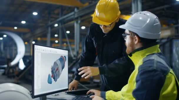 Uvnitř těžkého průmyslu inženýr pracuje na osobním počítači při povídání s vedoucí projektu. Navrhuje turbína / motoru v 3d Cad programu
