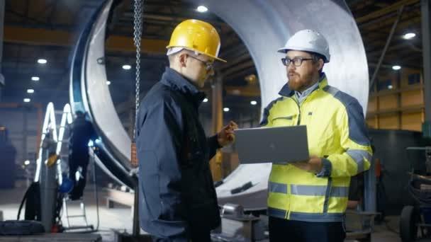 Uvnitř těžké tovární inženýr má Laptop a má diskuse s vedoucí projektu. Nosí tvrdě, klobouky a bezpečnostní vesty. V pozadí svařování / Kovovýroba probíhá
