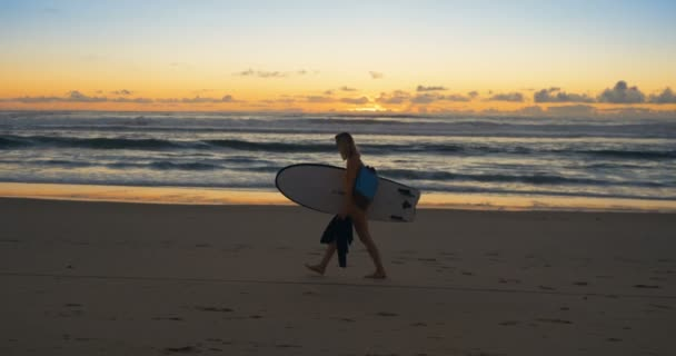 Side View Footage of the Beautiful Young Woman in the Swimsuit Walking Along the Beach while Carrying Surfboard. Sea with Waves and Sunset in the Background. Slow Motion.