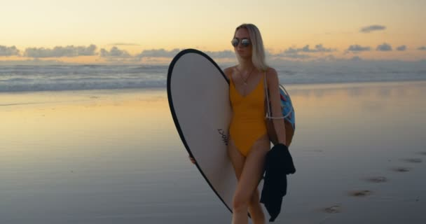 Beautiful Young Woman in the Swimsuit Walks Along the Beach while Carrying Surfboard. Sea with Waves and Sunset in the Background. Medium Shot in Slow Motion.