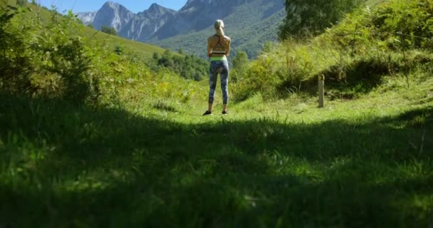 Back View of the Beautiful Fit Woman Runner in Sportswear Standing on the Trail Admiring Mountain View.