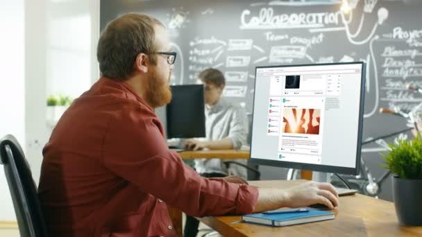 Kreative Büroangestellter surfen Seiten des sozialen Netzwerks, er führt einen Bildlauf durch seine Wand auf einem Personal Computer. Im Hintergrund stilvolle Kreativagentur Zimmer