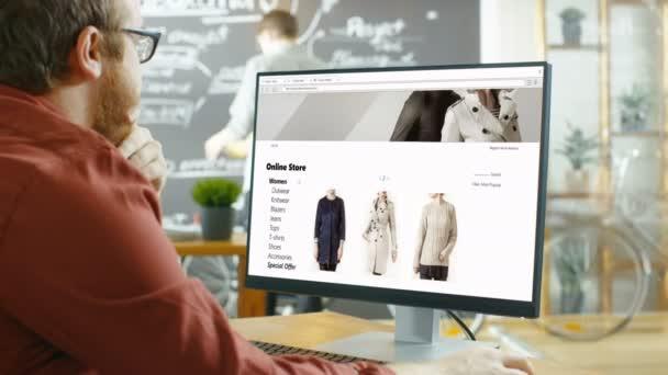 Web-Designer arbeitet auf einer Website für Online-Retail-Bekleidungsgeschäft. Er und seine Kollegen arbeiten in stilvollen Kreativagentur Studio mit Blackboard Wand bedeckt in Pläne und Zeichnungen.