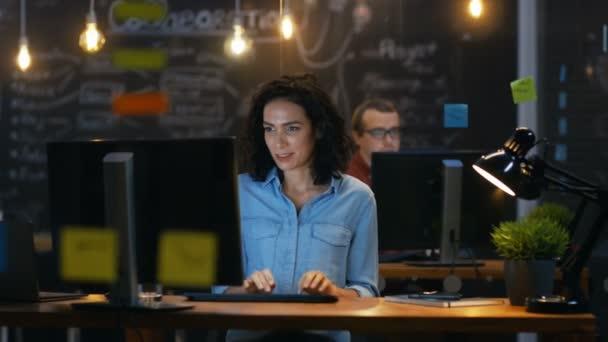 Krásné ženské Office zaměstnanec pracuje u stolu na osobním počítači. V pozadí spolupracovník v kanceláři kreativní