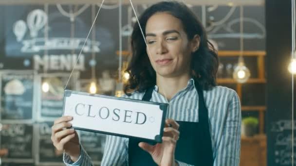 Krásná mladá Cafe majitel překlápění průčelí znak z blízkosti otevřené a vstřícné nové zákazníky do její moderní stylové kavárně při pohledu.