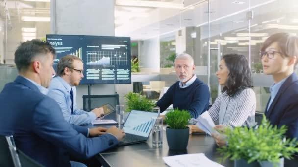 Im modernen Konferenzraum trifft sich der Vorstand jedes Jahr, eine bunte Gruppe von Geschäftsleuten diskutiert Statistiken und Arbeitsergebnisse. im Hintergrund Projektor, der das Unternehmenswachstum zeigt.