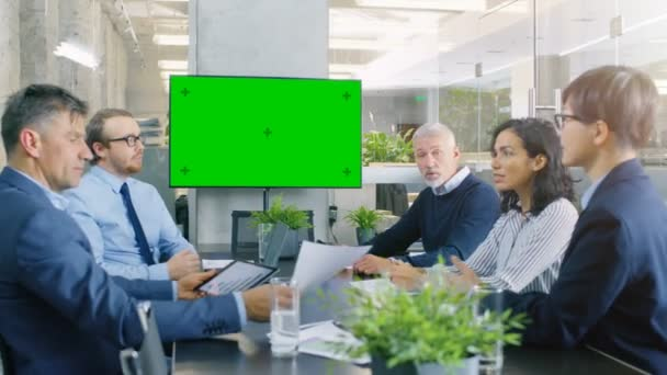 Diverse Group of Successful Business People in the Conference Room with Green Screen Chroma Key TV on the Wall. They Work on a Companys Growth, Share Charts and Statistics.