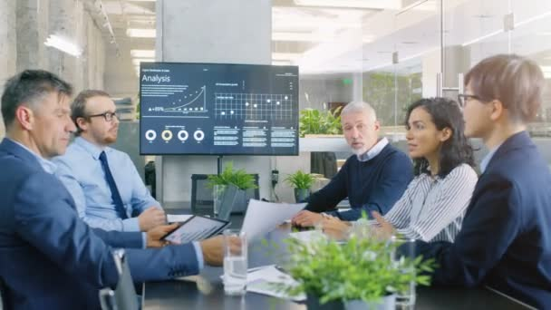 Diverse Group of Successful Business People in the Conference Room, Work on a Companys Growth, Share Charts and Statistics. In the Background Wall TV with Corporate Data on it.