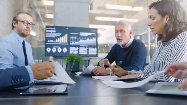 Různorodá skupina úspěšných podnikatelů v konferenční místnosti, práce na společnosti růst, podíl na grafy a statistiky. V pozadí zeď Tv s firemní Data na něm.