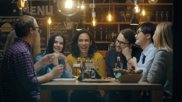 Diverse Group of Young People Have Fun in Bar, Have Conversation, Telling Stories and Jokes. They Drink Various Drinks. Theyre in the Stylish Hipster Restaurant.