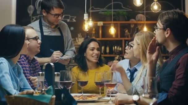 V baru / restaurace číšník bere objednávky z různorodé skupiny přátel. Krásné lidi pít víno a mít dobrý čas v tomto místě stylový.