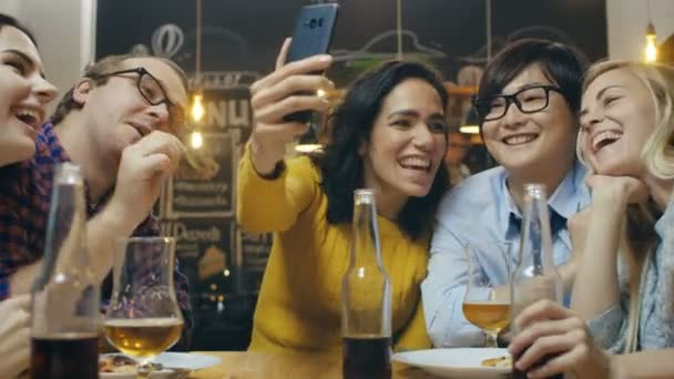 In the Bar/ Restaurant Hispanic Woman Makes Video Call with Her Friends. Group Beautiful Young People in Stylish Establishment.