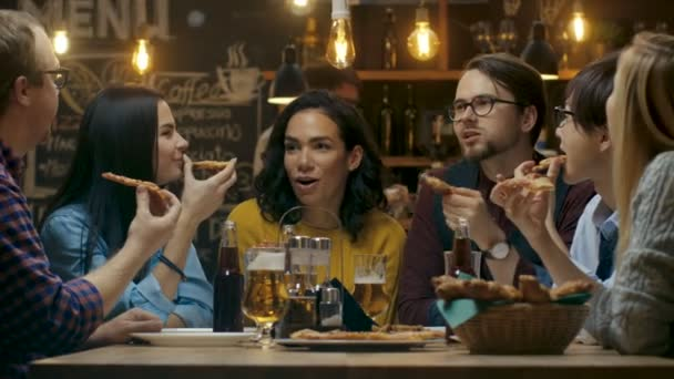 In the Bar/ Restaurant Group of Diverse Young People Eat Slices of Pizza Pie. They Talk, Tell Jokes and Have Fun in This Stylish Establishment.