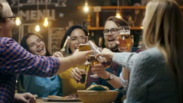Různorodá skupina přátel pronést přípitek a cinkání aktivována brýle s různými nápoji v oslavě. Krásné mladé lidi bavit ve stylovém baru / restaurace